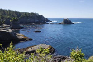 A rocky shoreline stretches out to meet the Pacific Ocean